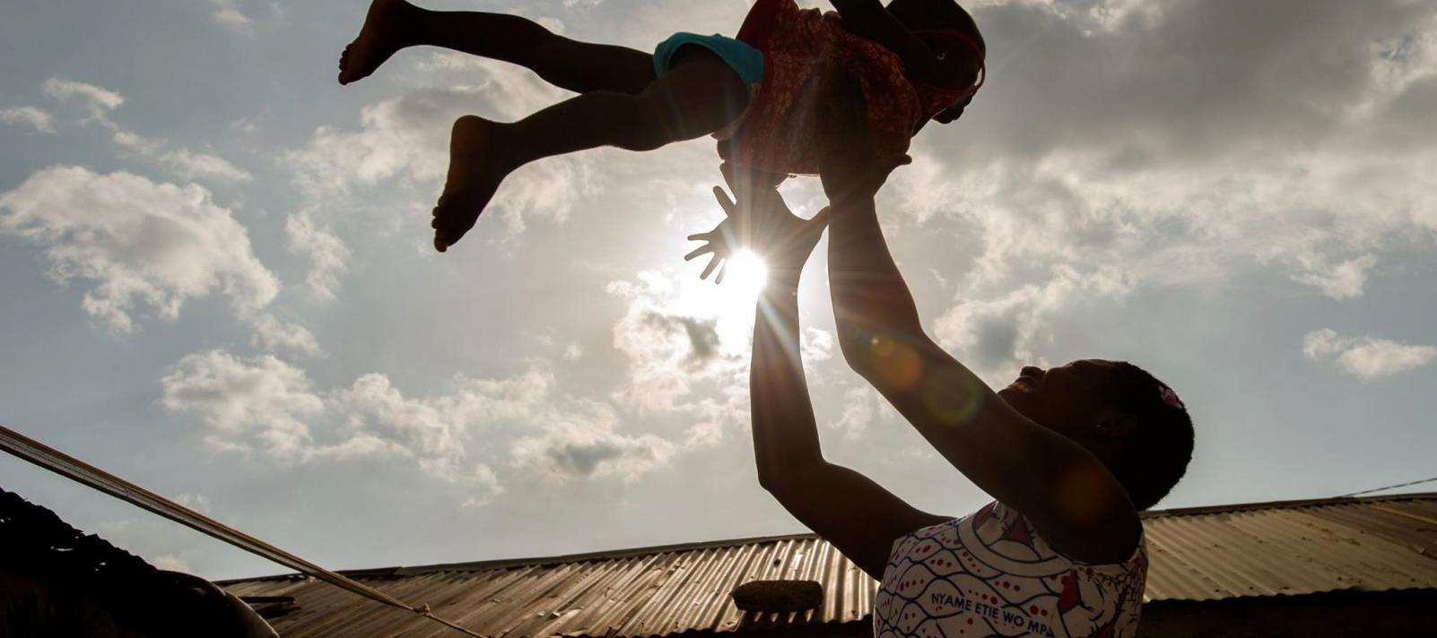 A mother and child playing, photographed against the sky