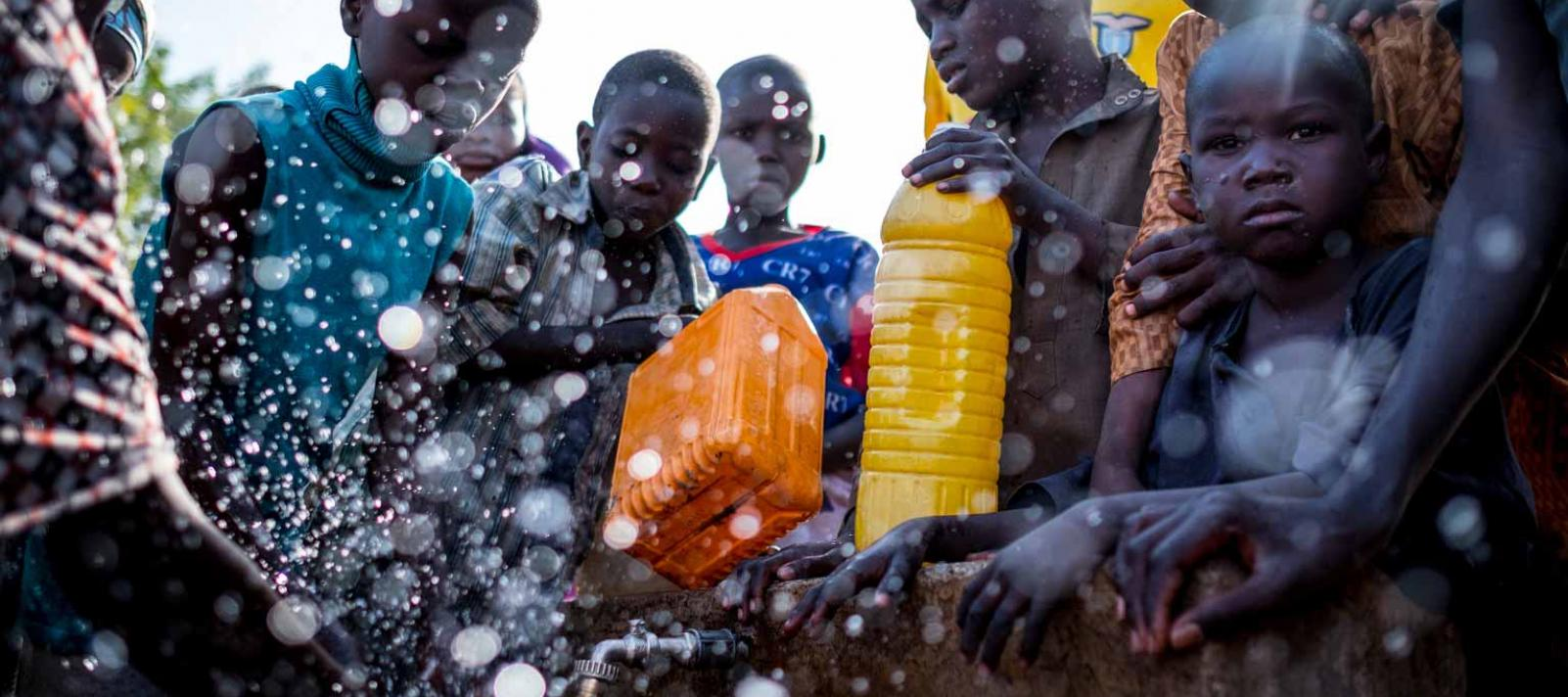 Water splashes as children fill jerrycans at an outdoor tap