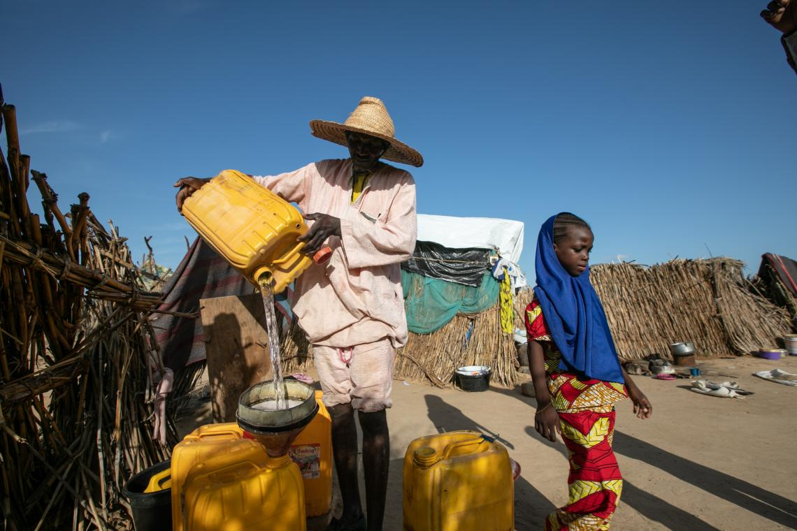A day labourer brings water to Hadjara's house while Sadia helps to collect the jerry cans.