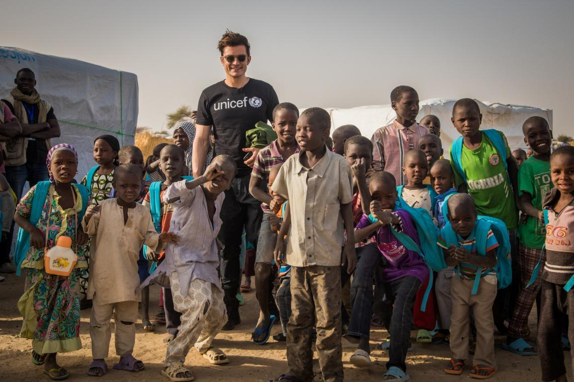 UNICEF Goodwill Ambassador Orlando Bloom (centre) stands with students following their classes at a temporary learning space at a camp for internally displaced people in Ngagam, near Diffa, Niger, Friday 17 February 2017.