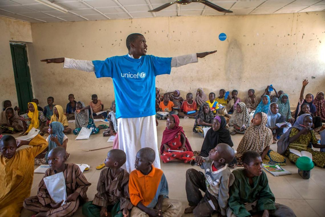 On 26 May, (standing), a teacher with his arms outstretched leads children in an activity at an informal learning centre in a UNICEF-supported safe space in the Dalori camp for internally displaced people, in the north-eastern city of Maiduguri in Borno State.