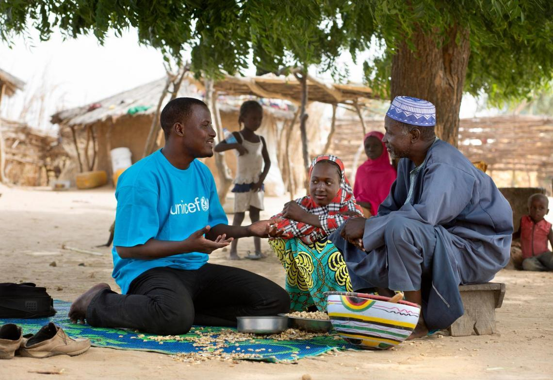 On 19 November 2015 in Rounga Hardo Oro in Maradi District, Issa Souleymane Madougou (in UNICEF t-shirt) from the Direction régionale de la population, de la promotion de la femme et de la protection de l'enfant de Maradi talks with the father (Abdou Garba, 55) of Habsatou (in red plaid).