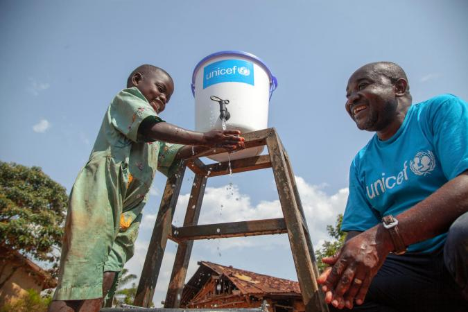 On 13 August 2018, Jean Marie Bofio, UNICEF's WASH Officer, talks with a girl as she washes her hands in order to prevent the spread of Ebola near Mangina, North Kivu, the Democratic Republic of the Congo (DRC).