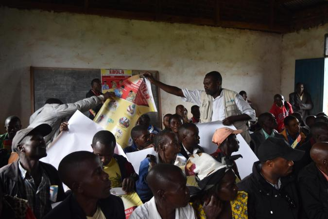 On 24 July 2018 in the Democratic Republic of the Congo, after raising awareness on how to prevent the spread of Ebola, UNICEF Communication for Development Officer Telly Dibindukidi distributes posters and pamphlets so that community leaders in Mangina, North Kivu, can educate their own communities.