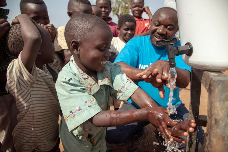 UNICEF's WASH Officer, demonstrates to children how to correctly wash their hands in order to prevent the spread of Ebola