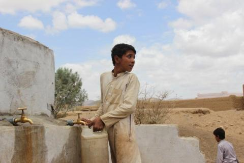 A boy collects clean water after the arrival of water trucks in AsSafra, Saada