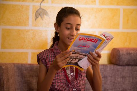 A girl reading a magazine in UNICEF child friendly space in Shabwah