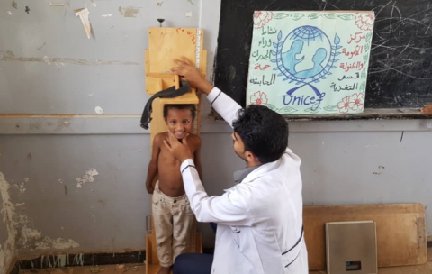 health worker measures the height of a boy