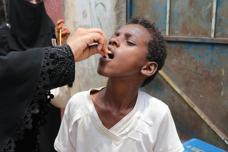 A child receiving his vaccine dose in Aden