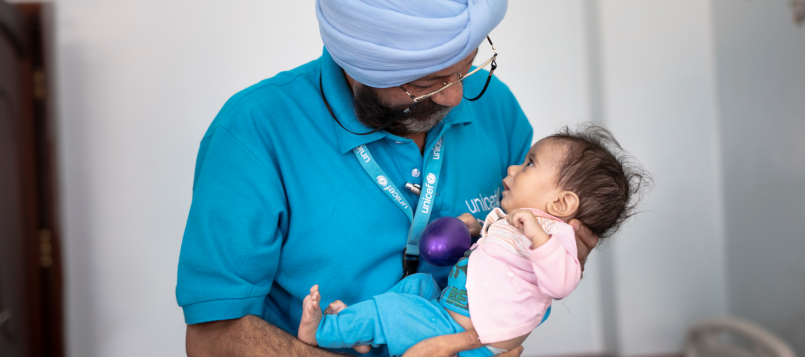 A UNICEF staff holding a baby.