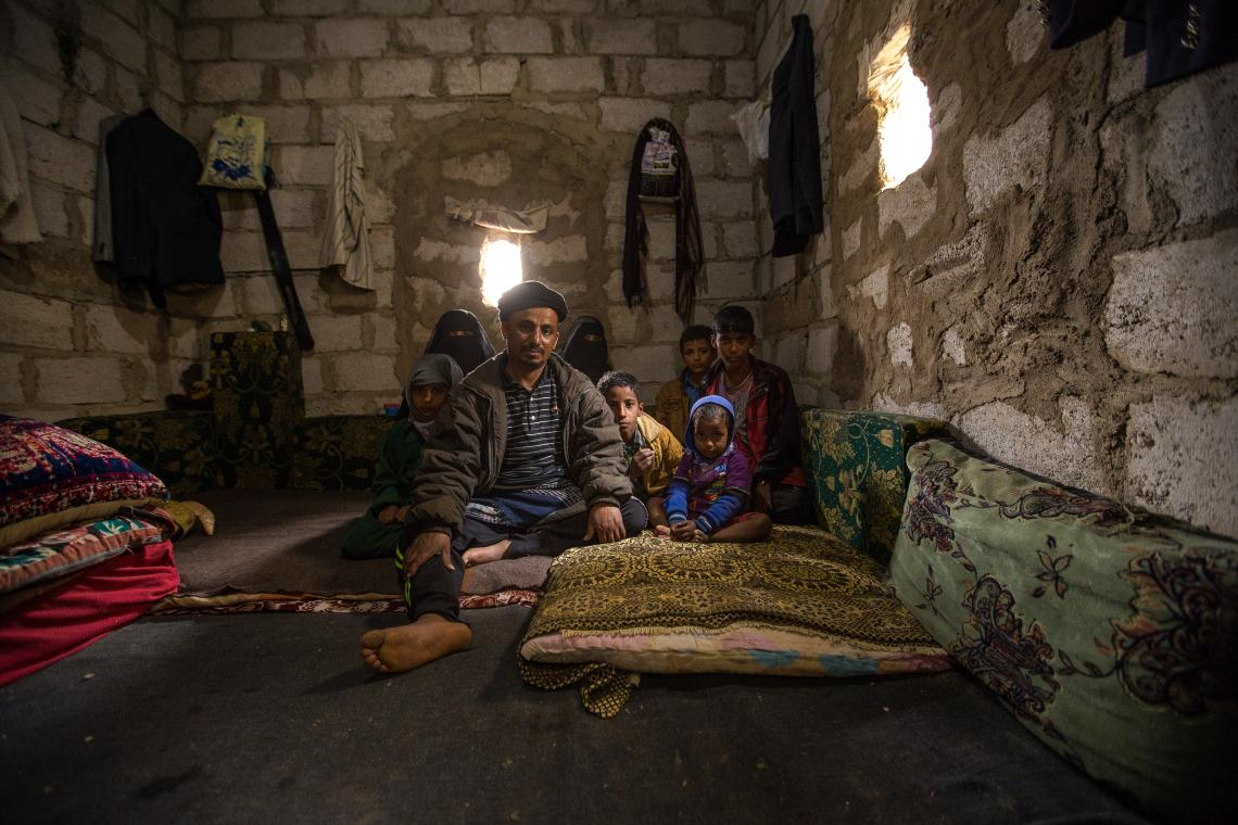 Faisal and his family in their house which consists of one single room with a place to cook and to sleep.