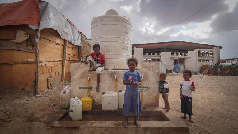 children at a water tank