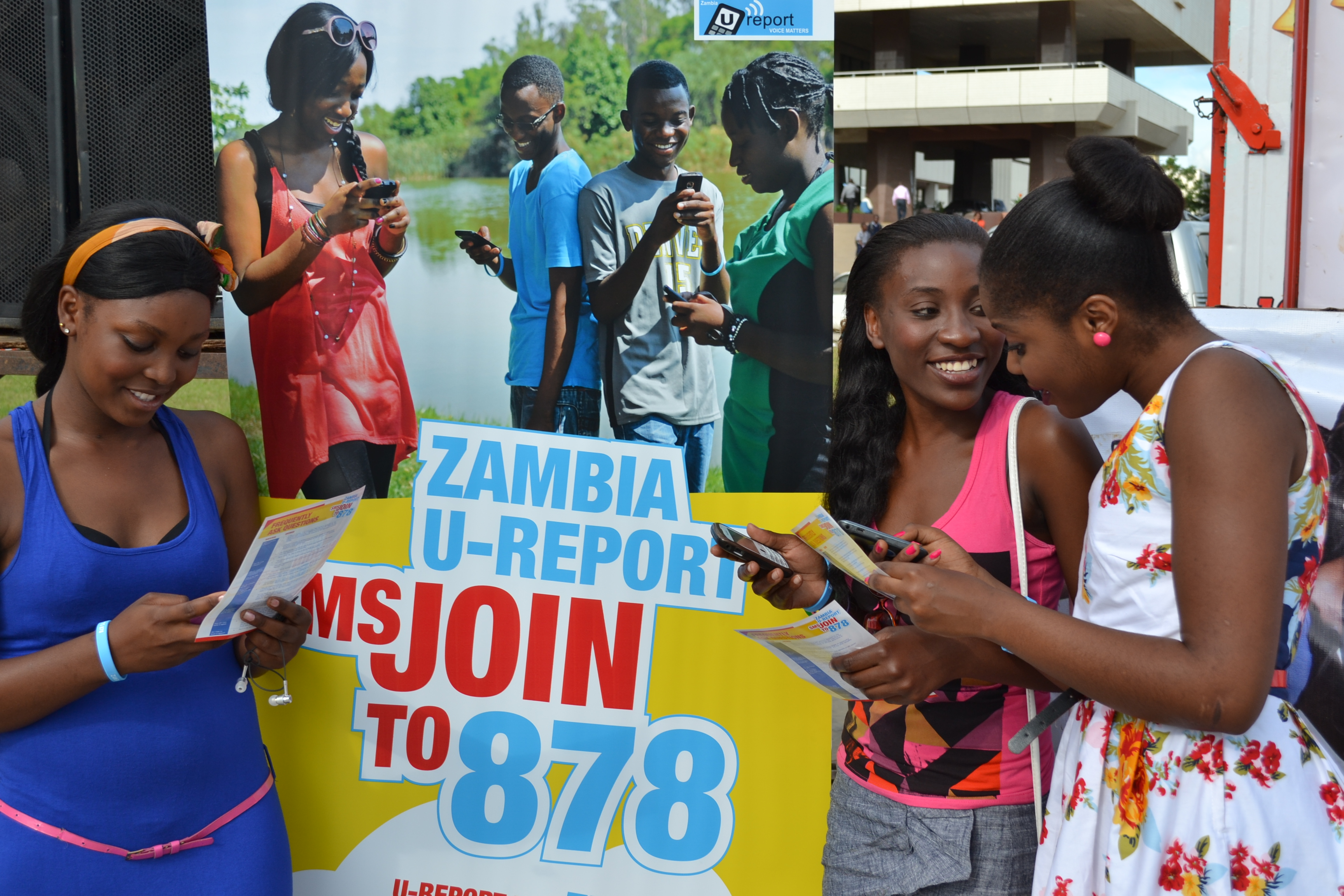 Three teenage Zambian girls next to U-Report pop-up