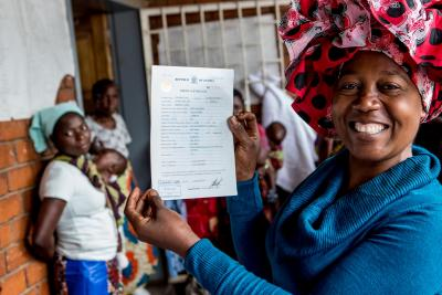 A mother holds her daughter's birth certificate after registering her birth