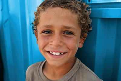 A Syrian boy smiling against a blue background