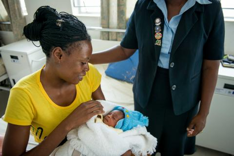 Mother on clinic bed with newborn and nurse in Zambia.