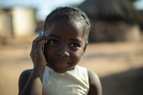 A small girl in a village on the telephone