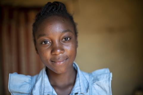 An adolescent Zambian girl looks at the camera with a smile