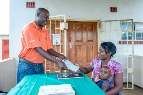 A mother receives her child's birth certificate in Zambia.