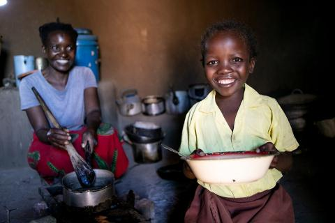 A school girl happily helps her mother prepare food in the kitchen