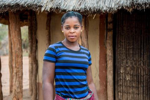 An adolescent woman stands in front a hut