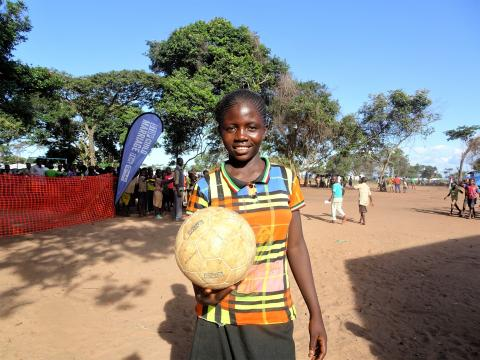 A teenage girl holds a football and smiles