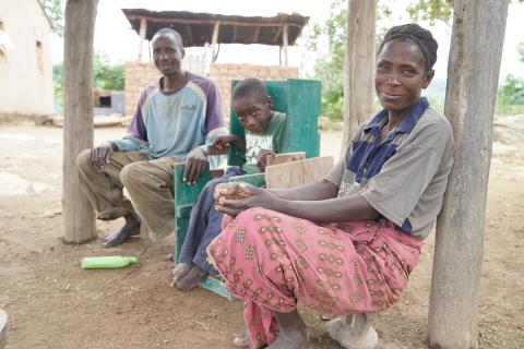 A rural family sit on stools outside in Zambia.