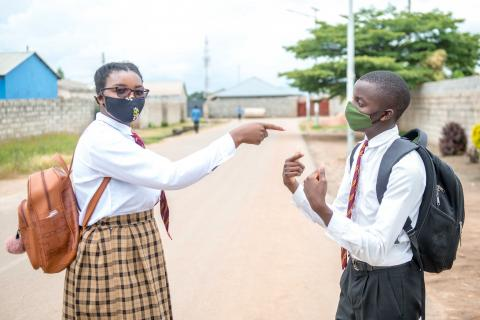 High school girl and boy in face masks in street in Zambia.