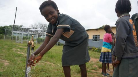 A school girl washes her hands outside