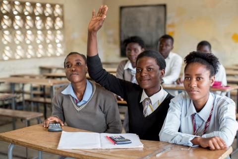 An adolescent school girl raises her hand in a classroom in Lusaka, Zambia