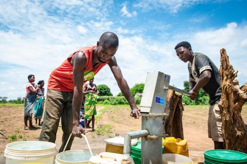Two men pump for water at a bore hole