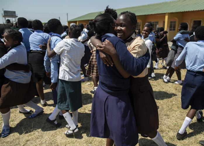 Girls hug each other during a careers camp activity in Zambia