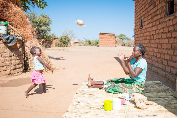 Mother sitting on ground passes ball with daughter