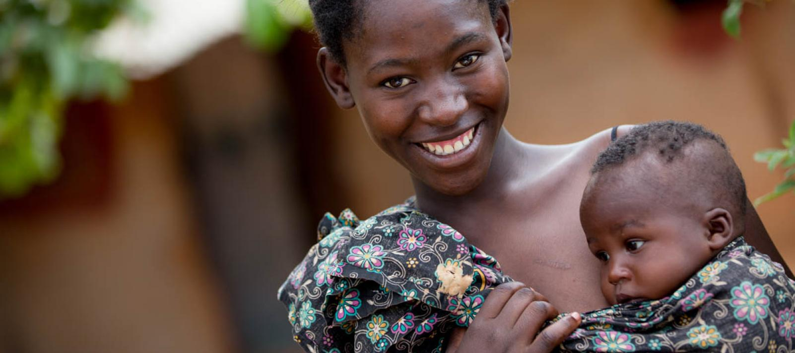 A smiling mother carrying a baby in a wrap