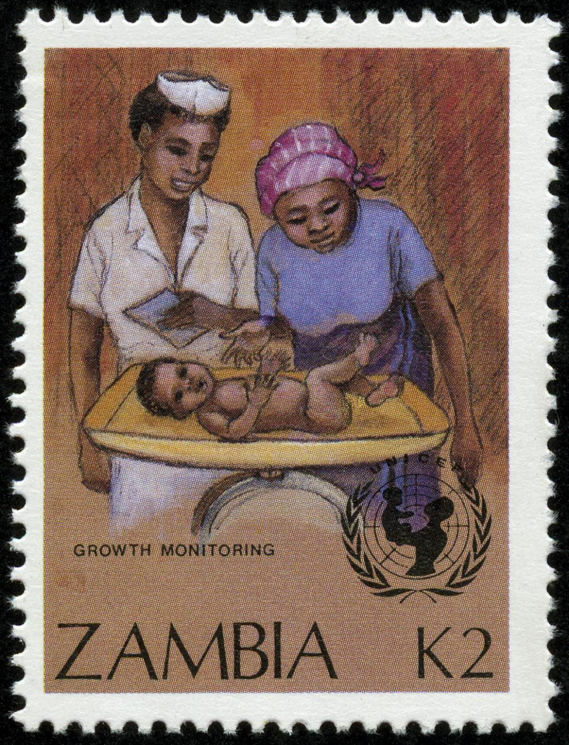 Postage stamp shows nurse and mother looking at baby
