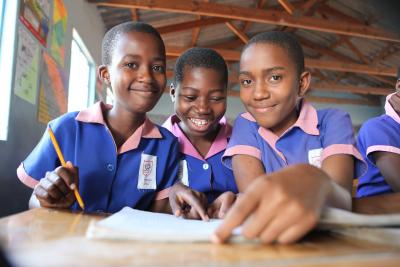 School children at Binga Primary school smile while reading books at the school