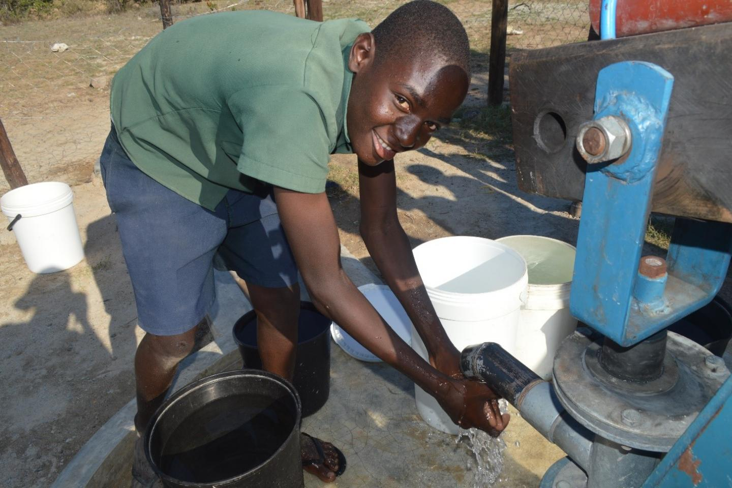 Mutsvene Sibanda washes his hands at the new borehole standpipe at his school, Zeruvi Primary
