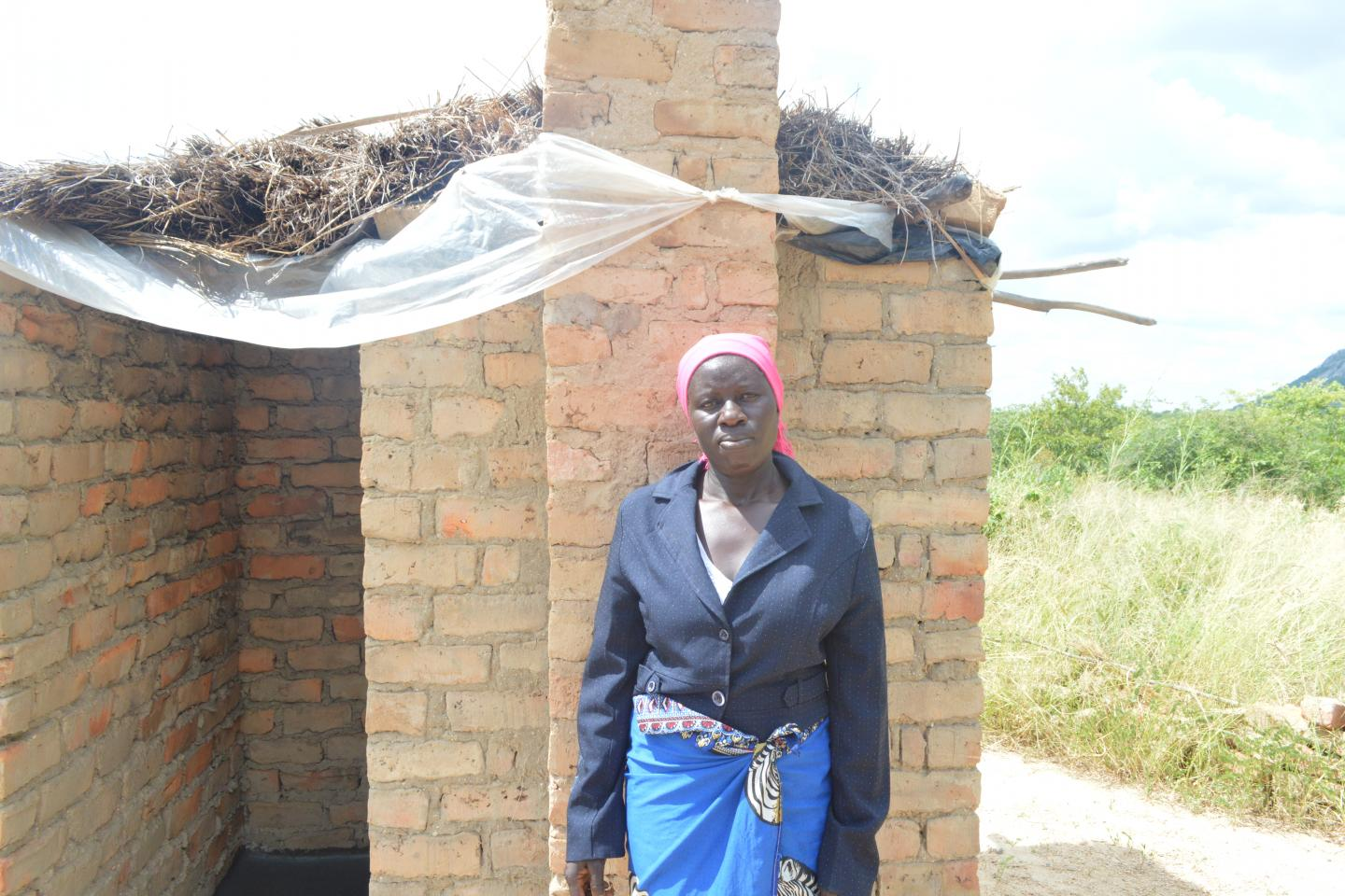 stands by the Teresa Ndemera latrine built with the support of her community's Sanitation Action Group (SAG).