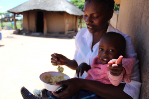 Thembekile Mthuthuk, 32, feeds her baby son with free porridge provided by the clinic.