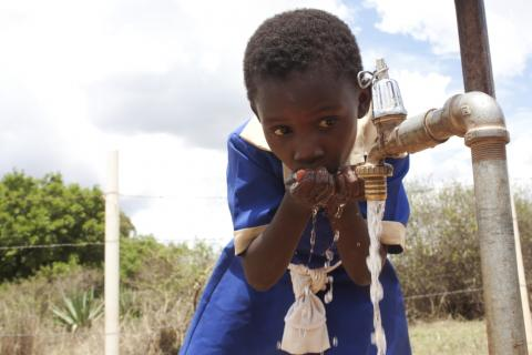 school girl drinking water from a tap