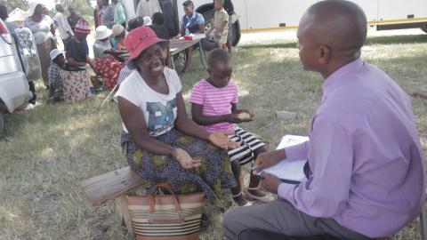 Gillian with her daughter, Nelia, speaks to a psychologist from the Ministry of Primary and Secondary Education (MoPSE) at the community outreach event.