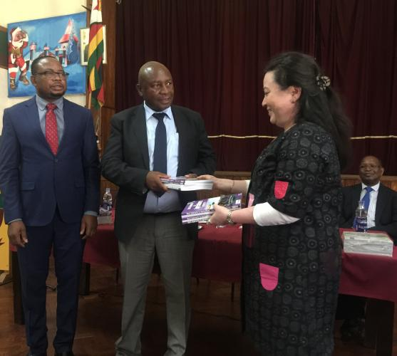 UNICEF Education Manager, Dr Chiharu Kondo (right) presents school textbooks to Deputy Minister Edgar Moyo, in the presence of Minister of Primary and Secondary Education, Prof. Paul Mavima (left).