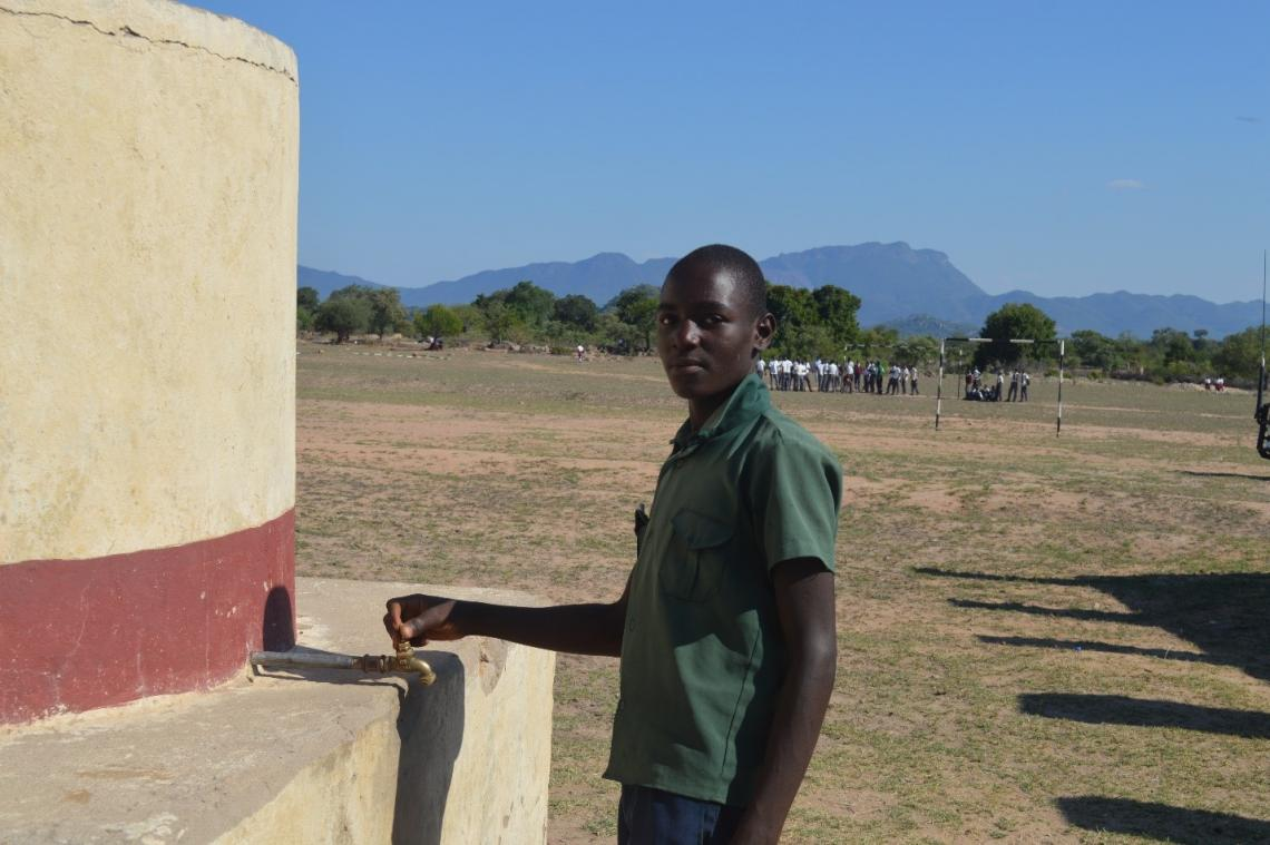Mutsvene Sibanda demonstrates one of the newly-installed standpipes at his school.