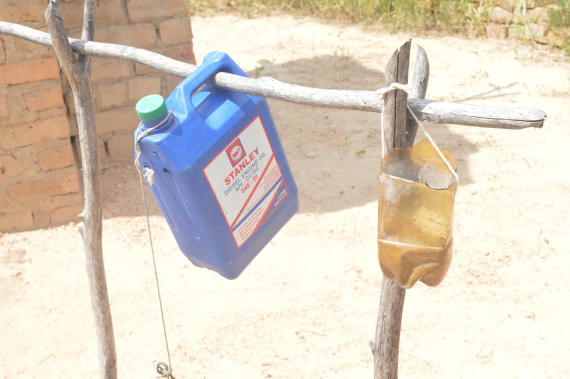Teresa's chigubu gear [tippy-tap], located next to the latrine.