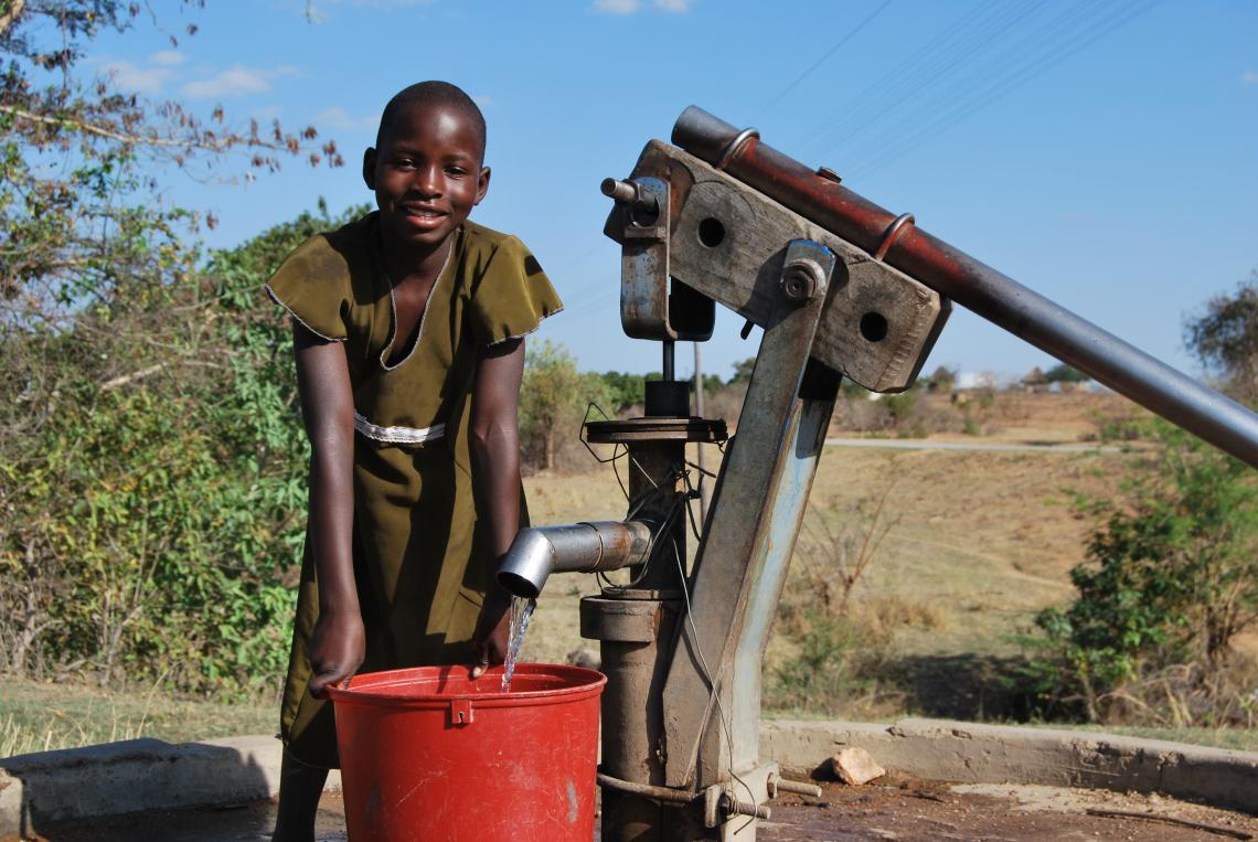 Girl standing by a borehole fetching water
